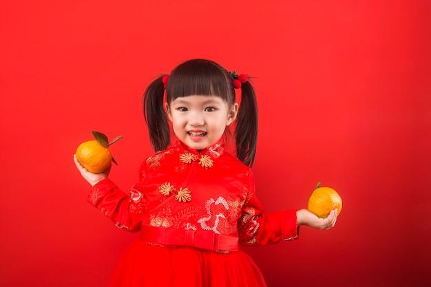 봄 축제를 위해 오렌지를 들고 중국 소녀