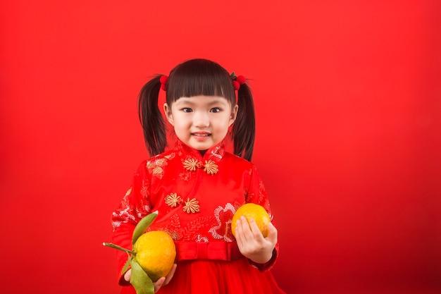 春祭りのためにオレンジを保持している中国の女の子