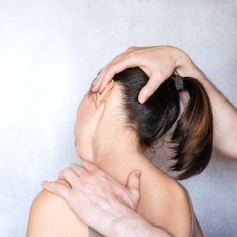 여성의 목을 조작하고 목 통증을 완화하기 위해 척추 조정을 시행하는 카이로프랙틱 의사