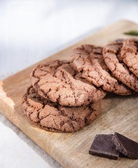 라이트 테이블에 나무 커팅 보드에 초콜릿 칩과 함께 초콜릿 쿠키. 매크로보기 및 닫기