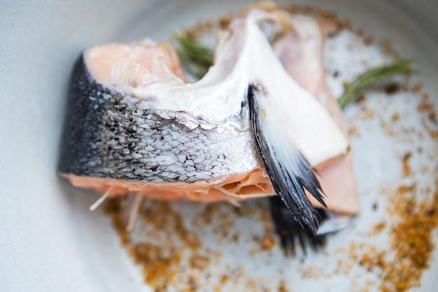 На тарелке лежит нарезанный кусок стейка из лосося вместе со специями и розмарином. процесс приготовления.