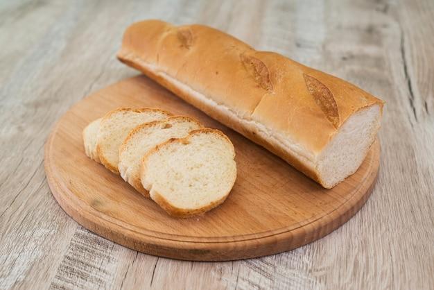 刻んだ全粒粉バゲットは木の板の上にあります。木製のテーブルの上にスライスしたおいしいフランスパン。