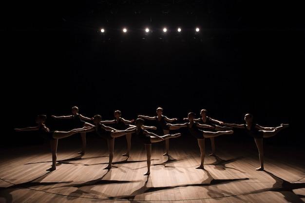 クラシックバレエ学校の舞台で練習している優雅なかなり若いバレリーナのグループの振り付けダンス
