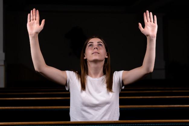 クリスチャンの女の子が教会で謙虚な心をもって祈って祈っています。