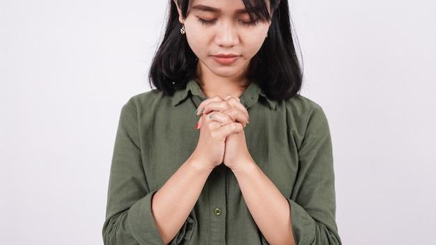 謙虚に孤立した白い壁を祈るクリスチャンの女性