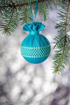 Елочный шар с узором висит на еловой ветке на серебряном фоне. новогоднее украшение.