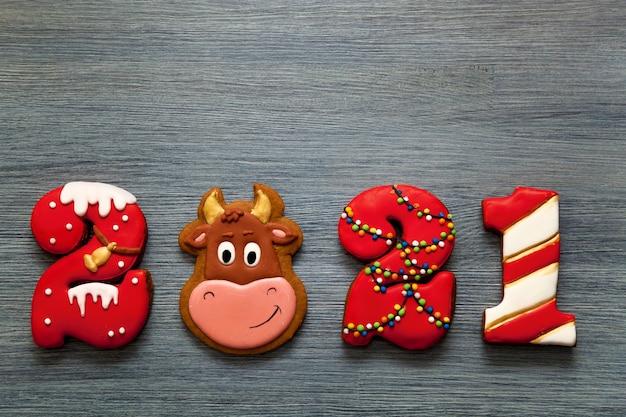 休日のクリスマスカード。 2021年の数字の形のジンジャーブレッドと灰色の木製の背景に新年の雄牛のシンボル。メリークリスマスと新年。