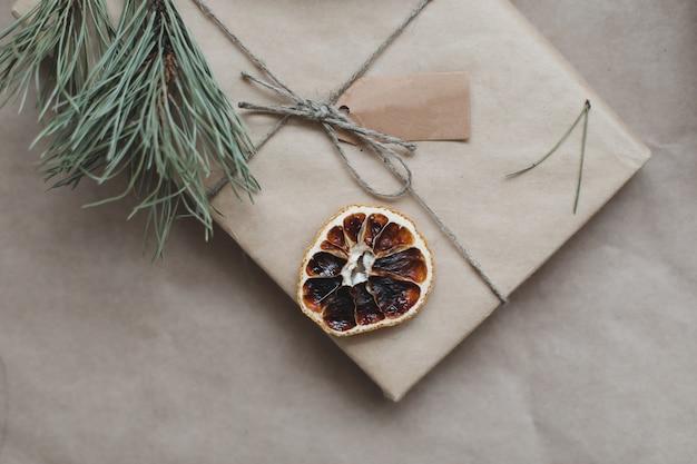 乾燥したオレンジスライスと松の枝で飾られたクラフト紙に包まれたクリスマスプレゼント