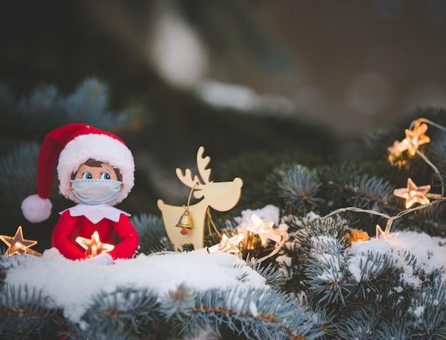 Елочная игрушка в медицинской маске сидит на ветвях заснеженного дерева со сверкающей звездой.