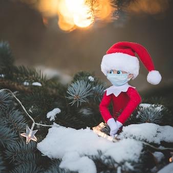 マスク付きのクリスマスのおもちゃは、花輪の輝く星と雪に覆われた木の枝に座っています