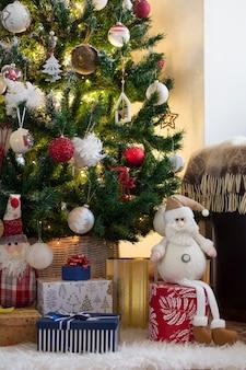 Елка, украшенная огнями и шарами, окружена множеством подарков и кукол.