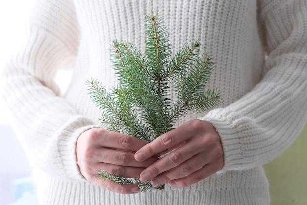 흰색 니트 스웨터에 여자의 손에 크리스마스 트리. 미니멀리즘.