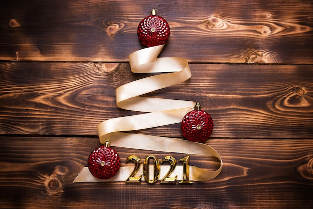Елка из золотой ленты с числами 2021 украшена красными воздушными шарами на темном деревянном фоне. плоская планировка. место для текста. новый год, шляпа санты.