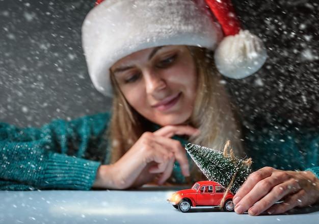 Елка привязана к игрушечной машинке на столе, девушка в шапке санты мечтательно смотрит на пишущую машинку.