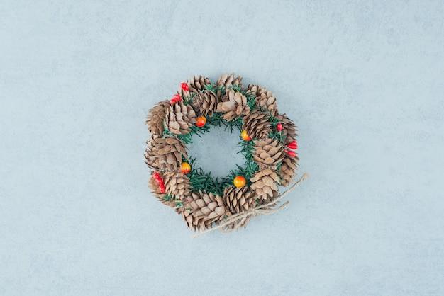 Рождественский венок из шишки на мраморном фоне. фото высокого качества