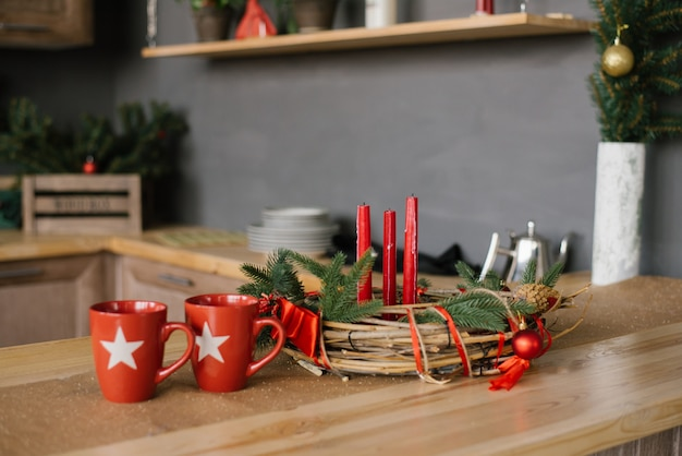 나무 테이블에 붉은 촛불과 부엌에 두 개의 빨간 머그잔 크리스마스 화환,