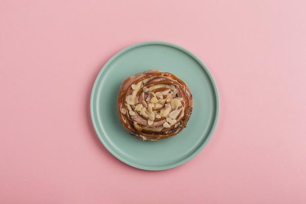 Булочка cinnabon с карамелью и дольками миндаля лежит в тарелке на розовом фоне. американская классическая булочка.
