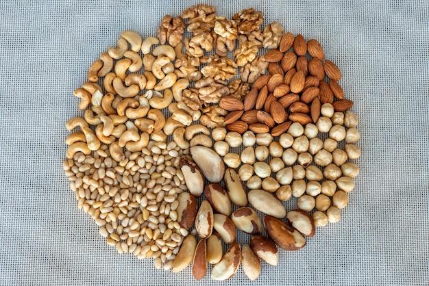 リネン生地のさまざまなナッツの輪、クローズアップ。クルミ、ヘーゼルナッツ、アーモンド、ブラジル、カシューナッツ、松の実のナッツカーネル