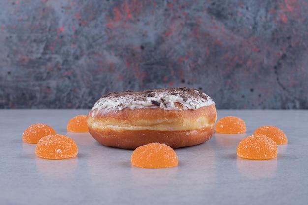 Круг мармеладов вокруг пончика на мраморной поверхности