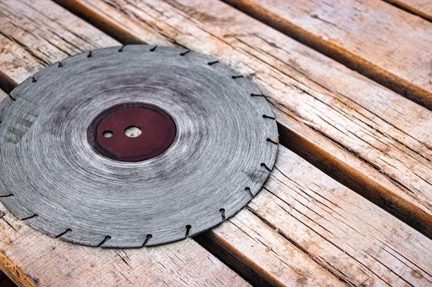 원형 톱날이 나무 판자 표면에 놓여 있습니다. 콘크리트와 석재를 절단하기 위한 오래된 다이아몬드 블레이드. 부드러운 선택적 초점입니다.