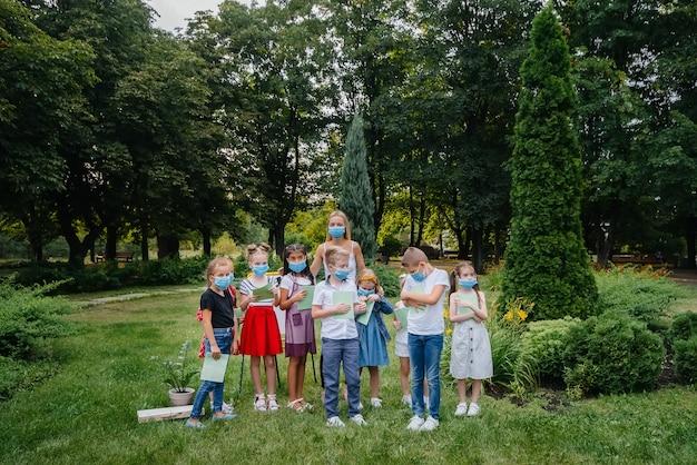 マスクされた学童のクラスは、流行の間に屋外トレーニングに従事しています