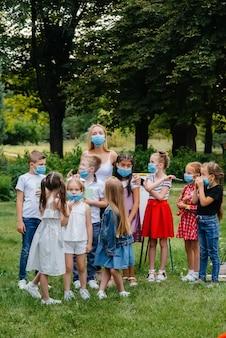 Класс школьников в масках занимается тренировками на свежем воздухе во время эпидемии