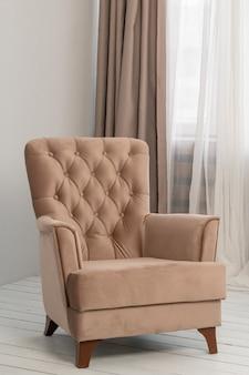 В комнате у окна стоит классическое бежевое кресло. за ней висят шторы и тюль.