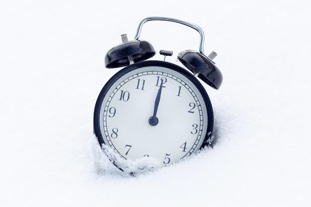 雪の中で古典的な黒い目覚まし時計。新年のコンセプト。時間は時計の12時です。