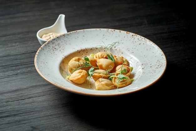 Классическое китайское блюдо - жареные пельмени с мясом и белым соусом на деревянном фоне.