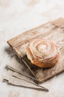 明るい背景にナプキンと木製のテーブルの上の古典的なシナボンパン。アメリカの古典的なパン。