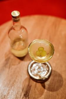 Классический сухой коктейль мартини в элегантном бокале купе, украшенный виноградом.