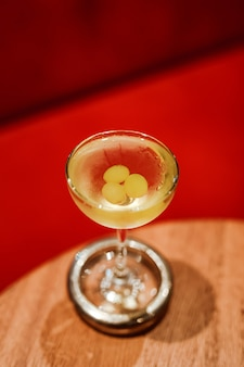 エレガントなクーペグラスにブドウを添えたクラシックなドライマティーニカクテル。