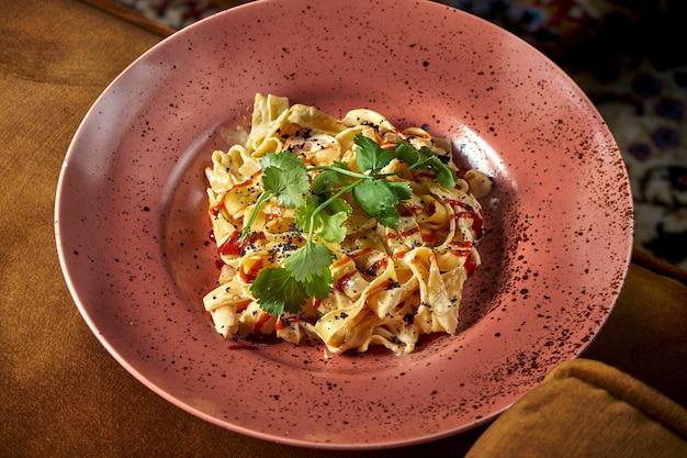 고전적인 이탈리아 요리-새우, 치즈, 화이트 소스를 곁들인 페투치니 파스타가 분홍색 접시에 담겨 있습니다. 레스토랑 음식. 위에서보기