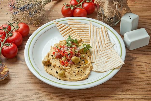 古典的な東洋の前菜料理-白いオリーブオイルと野菜のサルサを添えたひよこ豆のフムスを木製のテーブルの黒いプレートで提供しています。レストランの食べ物