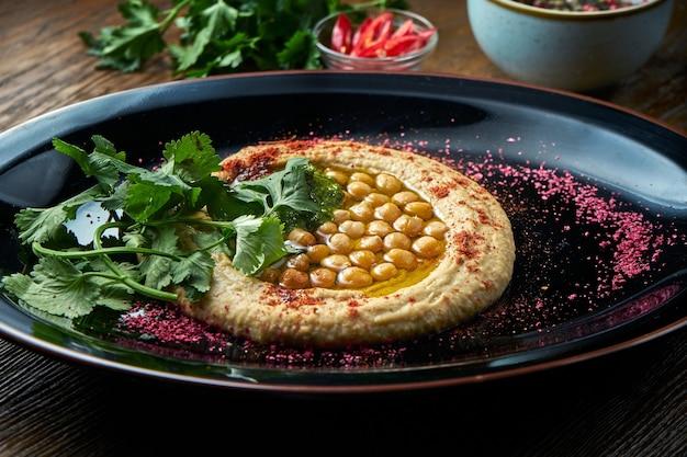 古典的な東洋の前菜料理-白いオリーブオイルを添えたひよこ豆のフムスを、木製のテーブルの黒いプレートで提供しています。レストランの食べ物