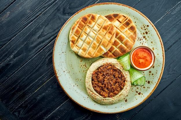 Классическое восточное блюдо - хумус из нута с оливковым маслом и мясным фаршем, подается с запеченным лавашем в тарелке на темной деревянной поверхности. вегетарианская пища. диета