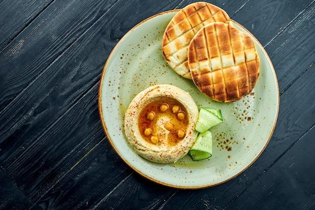Классическое восточное блюдо - хумус с оливковым маслом и нутом, подается с запеченным лавашем в тарелке на темной деревянной поверхности. вегетарианская пища. диета