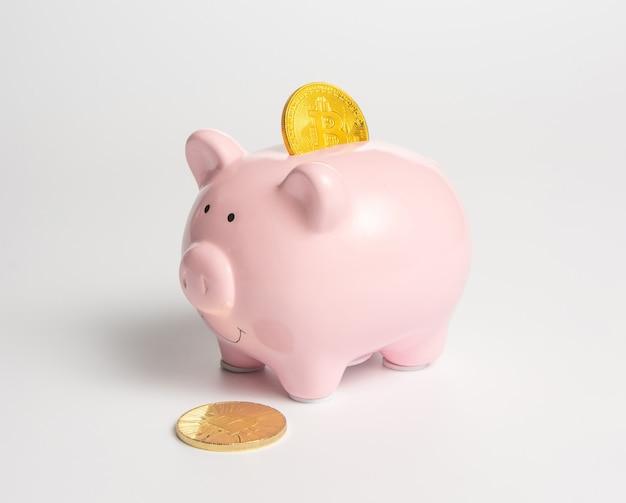 暗号通貨のシンボルが付いた古典的なピンクの貯金箱-ビットコインゴールドコイン