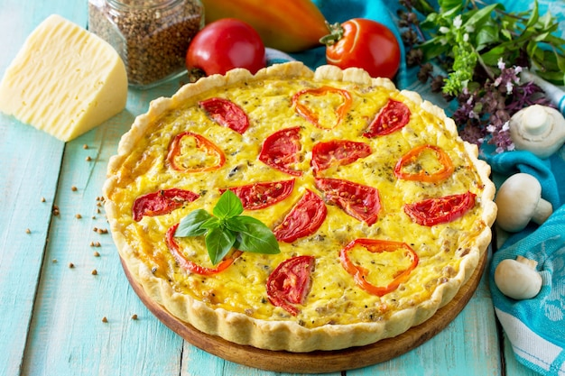 Классический лотарингский пирог с заварным кремом с гречишными грибами, паприкой, помидорами, сыром и яичной начинкой на деревянном столе копирование пространства