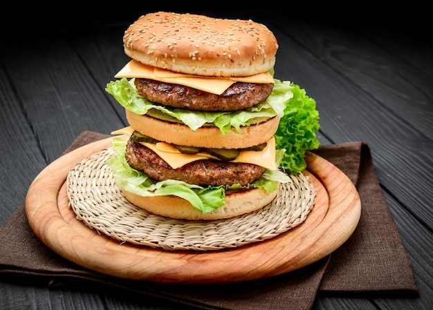 Двойной чизбургер в классическом стиле с двумя котлетами из говядины, соусом, листьями салата, сыром, солеными огурцами и луком на булочке с кунжутом