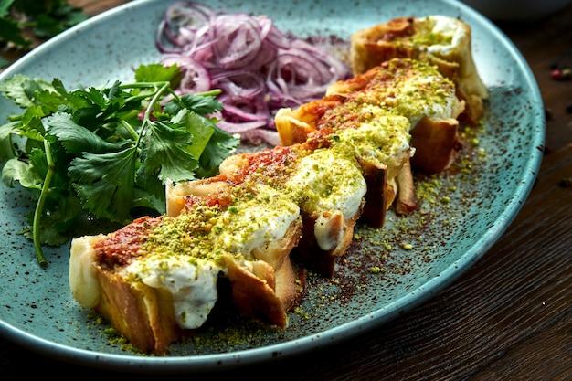고전적인 터키 요리는 빨간색과 흰색 피스타치오 소스를 얹은 치킨 케밥을 얇게 썰어 나무 테이블에 파란색 접시에 담아 제공합니다. 레스토랑 음식