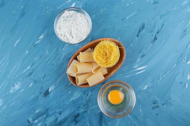 青の背景に巣麺の粘土板と小麦粉のガラスのボウル。