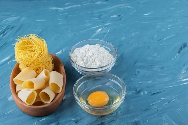 巣麺の粘土板と青の背景に小麦粉のガラスのボウル。