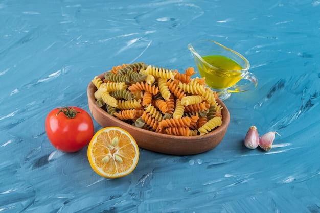 Глиняная доска сырых макарон с маслом и свежими красными помидорами на синей поверхности.