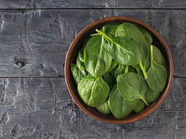 검은 나무 테이블에 시금치 잎으로 가득 찬 점토 그릇. 건강을 위한 음식. 채식주의 자 음식. 정상에서 본 모습.
