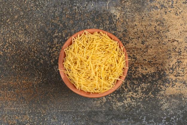 대리석 표면에 말린 생 당면 파스타로 가득 찬 점토 그릇.