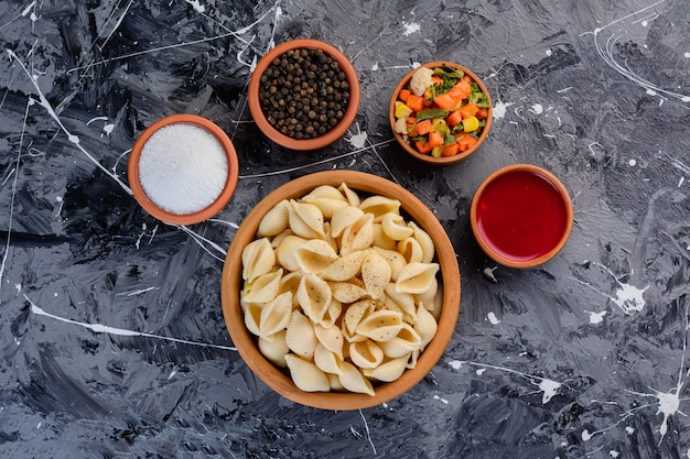 대리석 표면에 토마토 소스를 곁들인 쉘 파스타가 가득한 점토 그릇