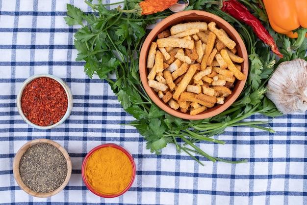テーブルクロスの上に野菜とブレッドスティックの粘土ボウル 無料写真