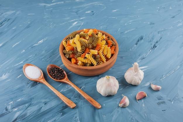 파란색 테이블에 마늘과 멀티 컬러 원시 파스타의 점토 그릇.