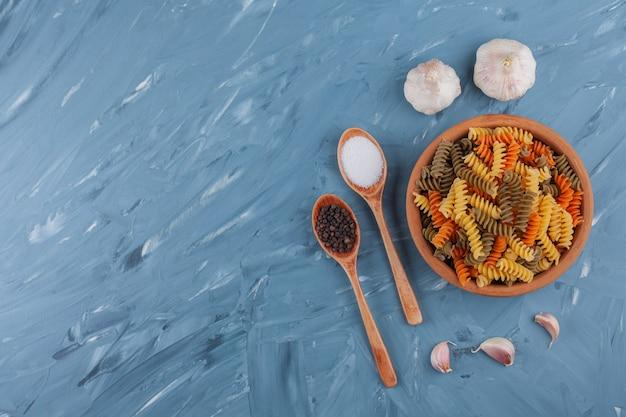 Глиняная миска разноцветных сырых макарон с чесноком на синем столе.